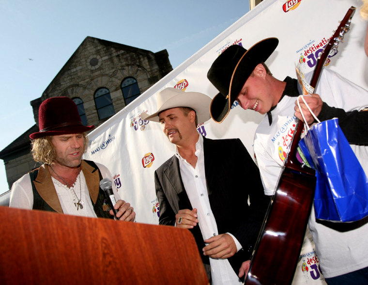 In this photo made available by Make-A-Wish Foundation of America, Big Kenny Alphine, left, and John Rich, center, also known as the country duo Big & Rich, welcome Make-A-Wish kid Brian Johnson, right, of Whitehall, Mont. to Nashville, Tenn. and present him with an autographed guitar. Brian's wish — to attend CMA Music Festival and meet his favorite country music artists — coincides with the launch of a new Make-A-Wish campaign.