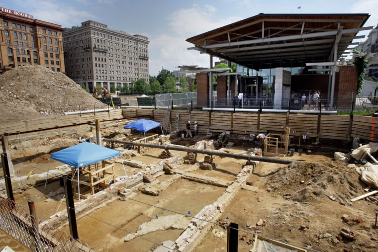 The remains of Colonial-era buildings, including the house that George Washington lived in when he was president, are exposed at an archaeological dig in front of the Liberty Bell Center, top right, in Philadelphia. Archaeologists have discovered a hidden passageway that was used by Washington's nine slaves.