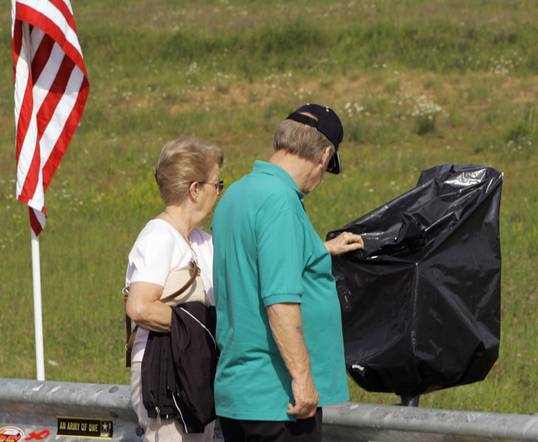 Visitors examine the garbage-bag-wrapped cash donation box Friday at the site of a temporary memorial for victims of United Flight 93 outside Shanksville, Pa.