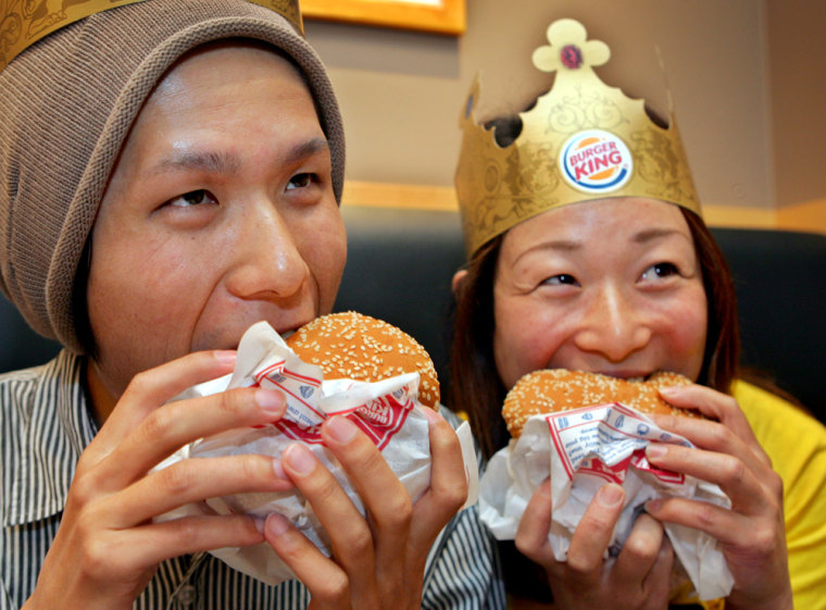Momoka Tanaka, right,and Daiki Hokotate, chow down on Whoppers after Burger King reopened in Japan after a six-year hiatus. The two were the first customers for thenew store in Tokyo's Shinjukudistrict.