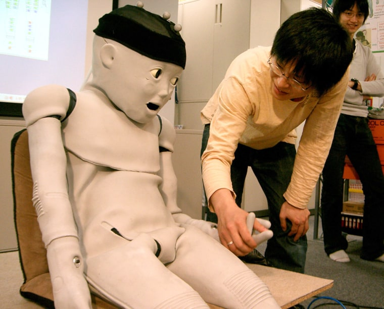 The Child-Robot with Biomimetic Body, or CB2, looks at Shuhei Ikemoto, an Osaka University student, when its hand is clasped by him during a demonstration of the toddler robot at a lab of the university in Osaka, western Japan.