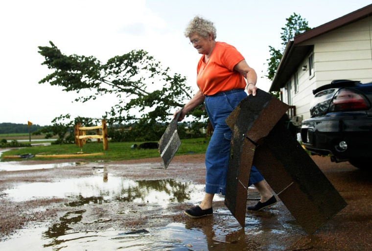 Marcella Kasper picks up shingles from her driveway Thursday in Reid, Wis., after a tornado touched down near her home.