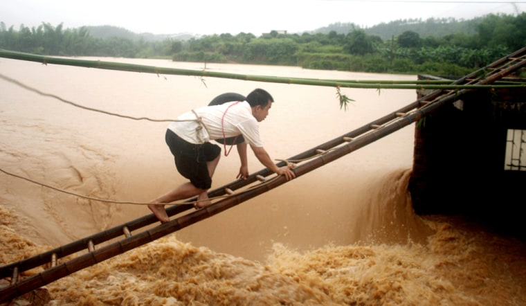 Aman tries to climb to a floodgate to unlock a valve in Zijin County of south China's Guangdong province June9.