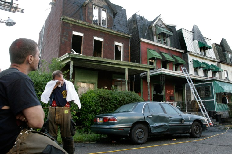 Pittsburgh firefighters take a break after fighting afire early Tuesday that killed five children.