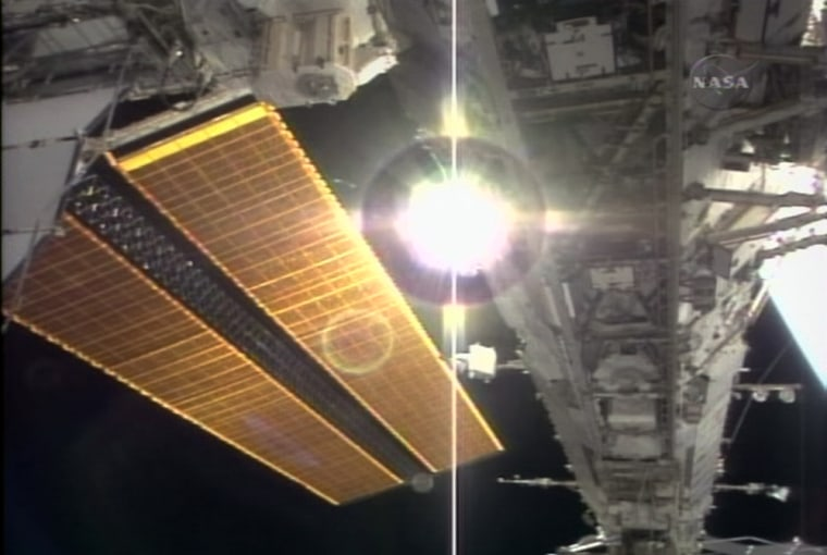 The international space station's new solar panels gleam golden alongside the truss structure installed by spacewalkers this week — with the sun shining through a gap.