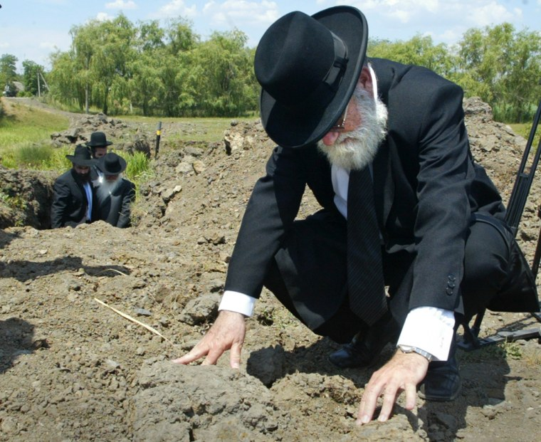 A rabbi from Israel checks the land at what Jewish leaders say is a mass grave of Jews slaughtered in Ukraine during World War II, in the village of Gvozdavka-1, on Monday, June 11.