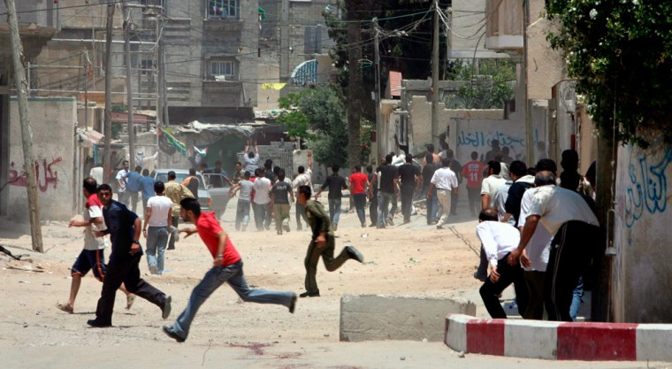 Palestinians run for cover with a car to the hospital