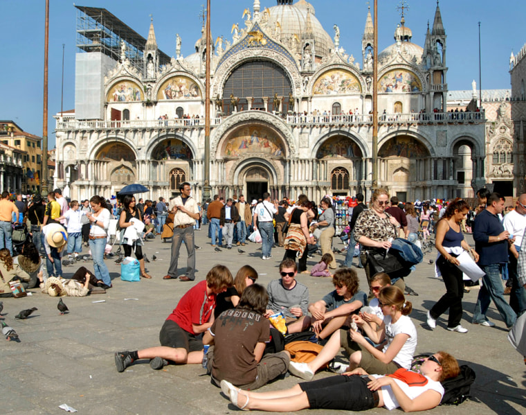 Tourists enjoy the sun in a crowded St. Mark's Square in Venice, northern Italy, with St. Mark's Basilica in the background. A message to visitors to Venice: No bare torsos in St. Mark's Square. No lounging on the monuments. And no feet dangling in the canals.