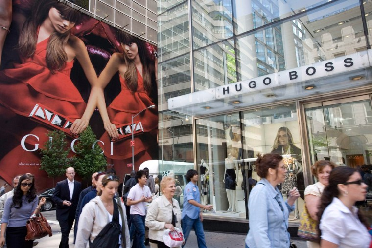 Shoppers stroll pass Gucci and Hugo Boss stores on Fifth Ave. While the average American worker's income increased 4.6 percent in 2006, the wealthy have enjoyed double-digit gains.