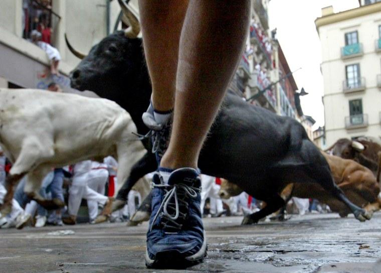 A young man runs from a bull during the Fiesta de San Fermin in Pamplona,Spain.