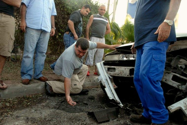 Israelis examine damage after a rocket fired from Lebanon hit the northern Israeli town of Kiryat Shmona onSunday.