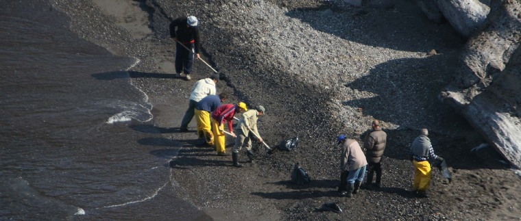 Clean-up crews use shovels to remove oil from a pebble beach on Santorini, Greece, in this file photo.