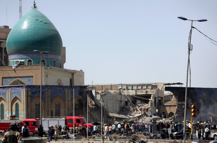 Residents gather at the site of a bomb attack in Baghdad
