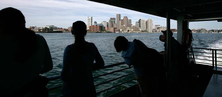 People look at the Boston skyline from a ferry heading to Spectacle Island in Boston.