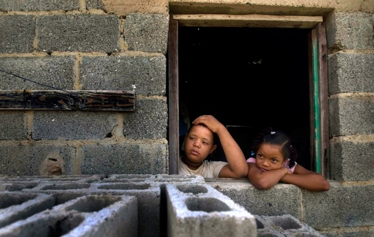 Two children look out on June 15 from their home in Haina, Domincan Republic, a town considered among the world's most polluted.