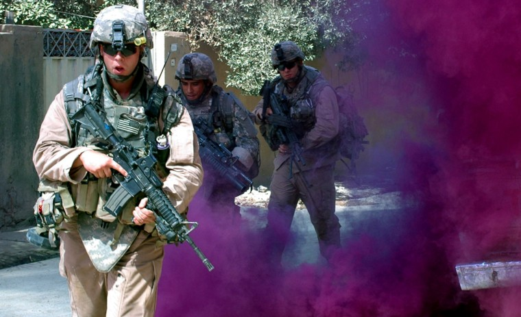 Soldiers with the 3rd Stryker Brigade Combat Team, 2nd Infantry Division, use a smoke grenade for concealment while moving to their next location in Baqouba, Iraq, on Tuesday. They are part of the offensive pushing out from Baghdad.