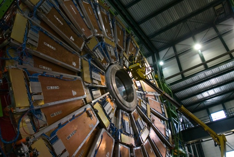 A worker on a crane checks muon detectors on a slice of the Compact Muon Solenoid during the construction of the Large Hadron Collider.