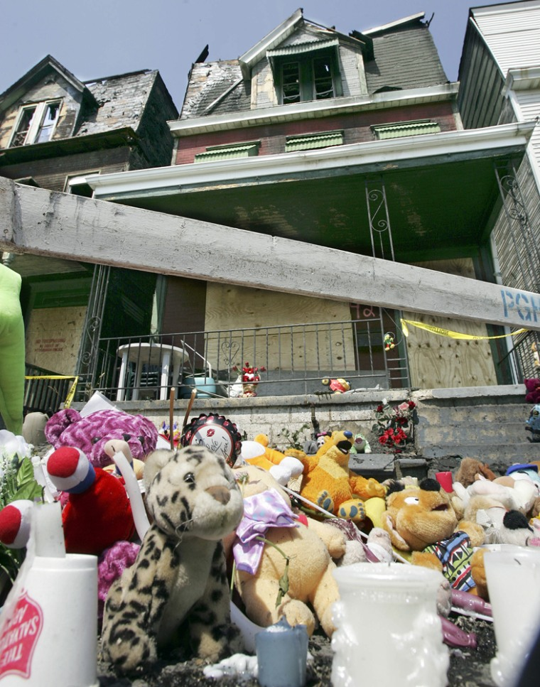 A pile of stuffed animals stands in front of two row houses Wednesday, June 13, a day after a fire killed five young children in Pittsburgh.