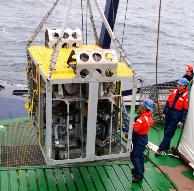 """The new robotic underwater vehicle named """"Camper"""" is maneuvered on the stern of the icebreaker Oden during a test cruise in the Arctic Ocean. Scientists plan to use it and other newly developed robots to sample new life they believe may be found along a series of underwater hot springs on rugged Gakkel Ridge in the Arctic."""