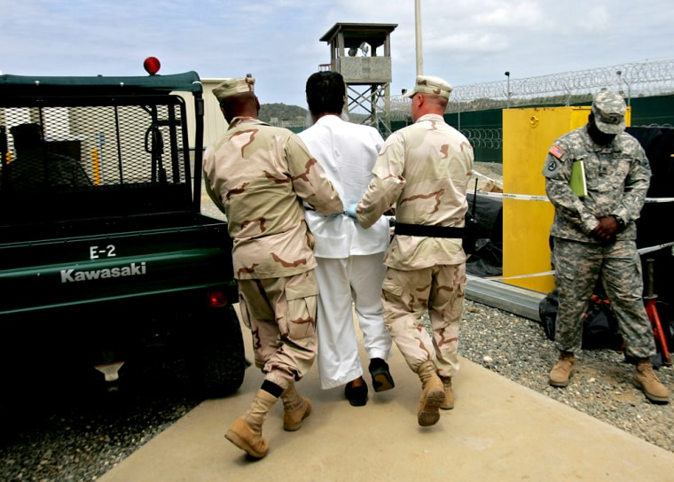 A Guantanamo detainee, center, is escorted by U.S. military personnel on the grounds of the detention facility at Guantanamo Bay.