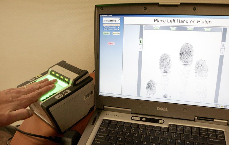 A man demonstrates the new 10-fingerprint scanner at the American Embassy in Brussels on June 25. The U.S. Department of Homeland Security is currently transitioning from collecting two fingerprints, digital and inkless, to collecting 10 fingerprints from foreign travelers going to the United States.