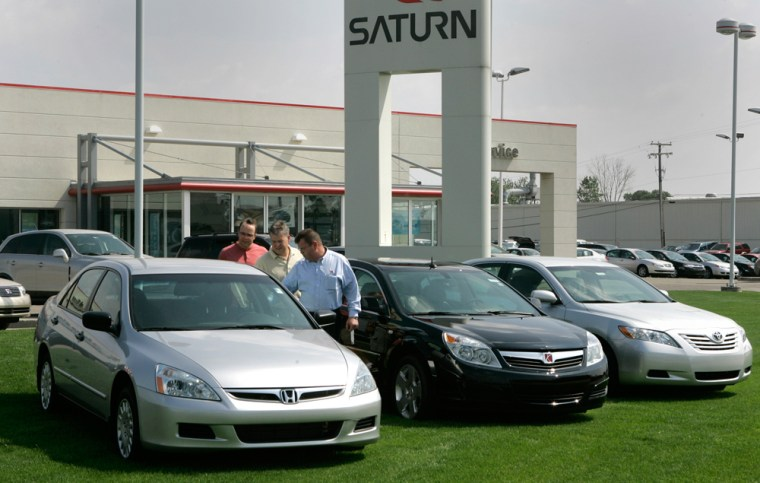 Vince Olsen, center, the manager of a Saturn dealership in Troy, Mich., comparesa Honda Accord, left, with a Saturn Aura, center, and a Toyota Camryas part of a promotion to boost Aura sales.