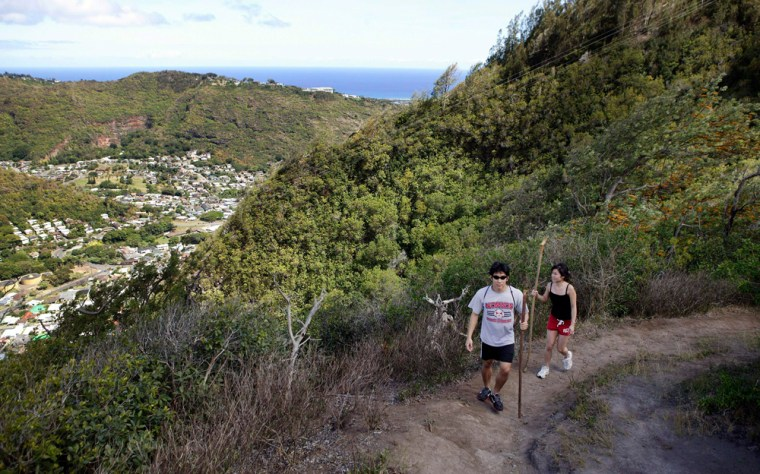 With Palolo Valley and the Pacific Ocean in the background, hikers walk the Waahila Ridge Trail, in Honolulu. Oahu trails can bring hikers in touch with the true beauty of the state's most populous island.