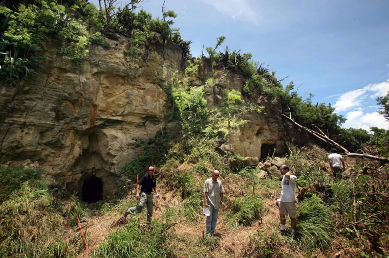 """Team members from the Joint POW and MIA accounting command walk outside two cave openings on the southwestern wall of """"Hill 362A"""" on Iwo Jima island on Wednesday."""