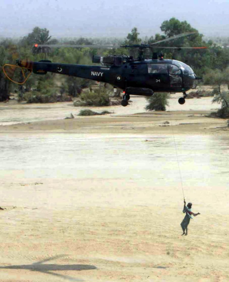 A Pakistani navy helicopter winches a fl