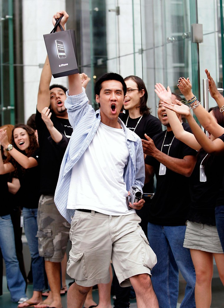 Surrounded by cheering Apple Store employees, one of the first iPhone buyers leaves the store on Fifth Avenue in New York