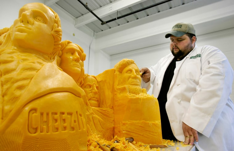 Cheesecarver and winemaker Troy Landwehr puts the finishing touches on a sculpture of Mount Rushmore carved from a huge block of cheddar cheese, on Friday in Little Chute, Wis.
