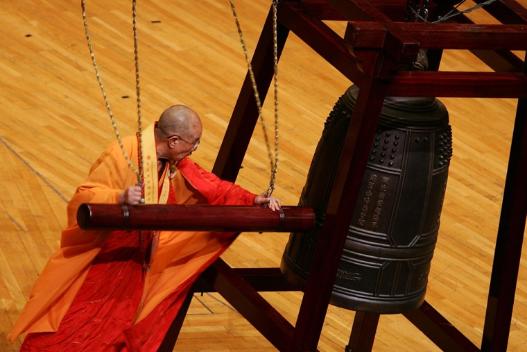 A Buddhist monk tolls a bell during a ceremony to pray for a better future in Hong Kong moments before the stroke of midnight Sunday, the 10th anniversary of Hong Kong's handover to Chinese rule from British colonial power.
