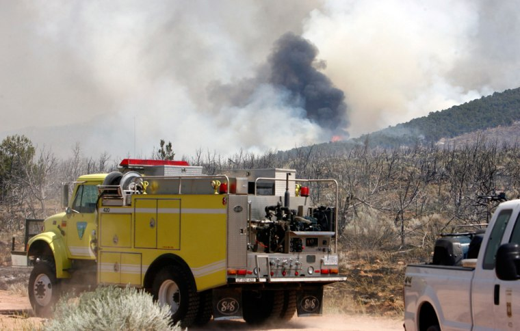 Smoke rises in the distance as a wildfire burns near Roosevelt, Utah, on Sunday.