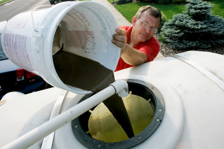 """Rich Staudt of Total Landscaping Care pours organic """"compost tea"""" he has just brewed into a a sprayer June 27, 2007, in East Meadow, N.Y. Staudt is one of a growing number of landscapers on Long Island and elsewhere who have embraced organic lawn care as an alternative to pesticides and other chemicals."""