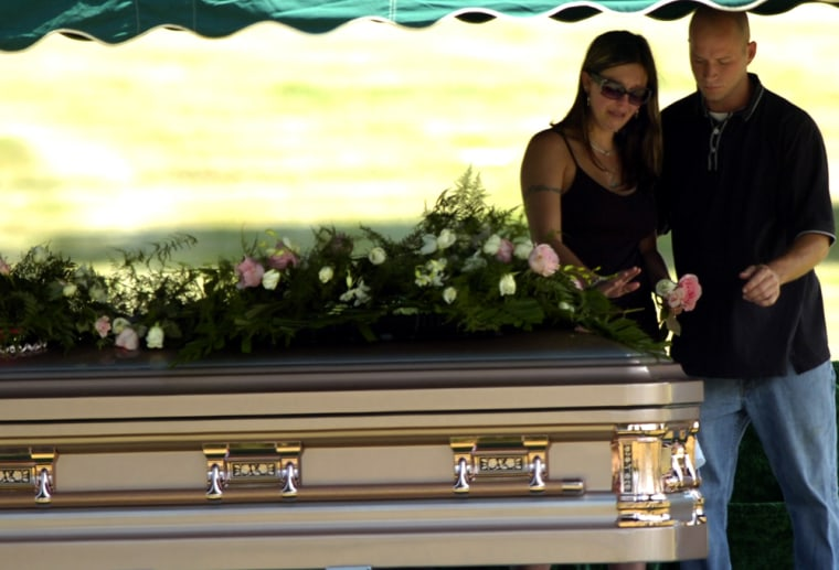 Sarah Crislip is escorted by Scott Sander from the casket of her high school friend, Jessie Davis, following a graveside service at Greenlawn Memorial Park Saturday in Akron, Ohio.