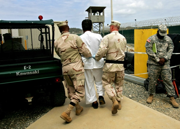 A detainee is escorted by U.S. soldiers at the detention facility at Guantanamo Bay Naval Base in Cuba.