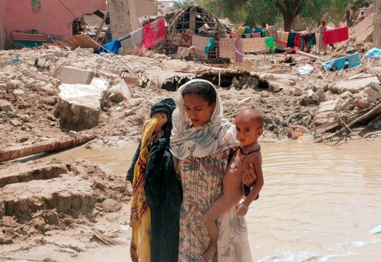 A flood victim wades through floodwater in Turbat