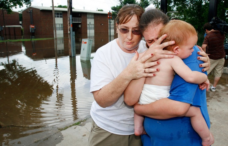 Crystal Clayburg, left, hugs friend Amber Lejk and Lejk's one-year-old daughter Mina Loghry after Lejk and three of her four children were rescued from their home by boat in Miami, Okla., on Tuesday. Lejk's fourth child was rescued a short time later.