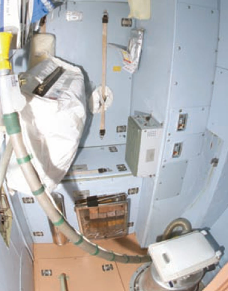 The international space station's zero-gravity toilet relies on suction for operation. In this picture of the compartment, the toilet seat is at lower right.