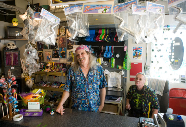 Larry Welz, left, and his wife, Sharon, talk about the UFO phenomenon in Roswell, N.M. in their souvenir shop, The Roswell Space Center. The Welzes said customers often complain there's not enough to satisfy their appetites for UFO fun.