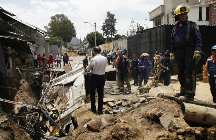 Rescue workers stand by a 45 foot deep sinkhole that swallowed a stretch of street in Mexico City onSunday. It began as a giant crack late Saturday in the eastern Iztapalapa borough and rapidly worsened when the ground collapsed, swallowing a car, the facade of a one-story brick building and pavement. One man is feared dead.