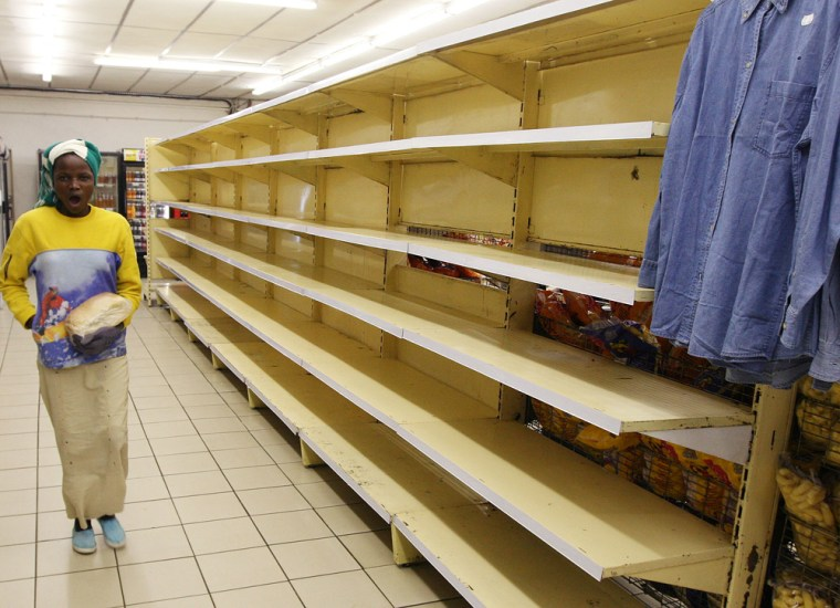 A woman walks past empty supermarket shelves in Harare July 2.