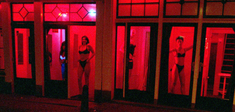 Prostitutes stand behind red-lit windows, waiting for customers in Amsterdam's Red Light District in 1997.