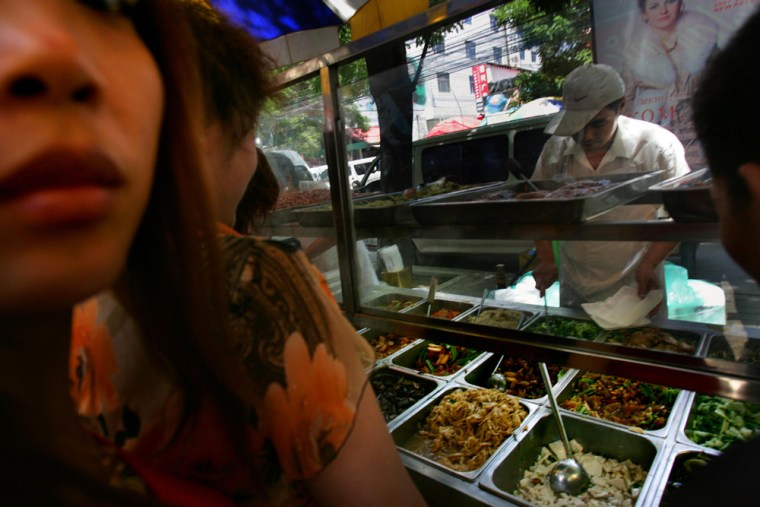 Customers line up to buy food from a street vendor in Beijing, China, on June 5.