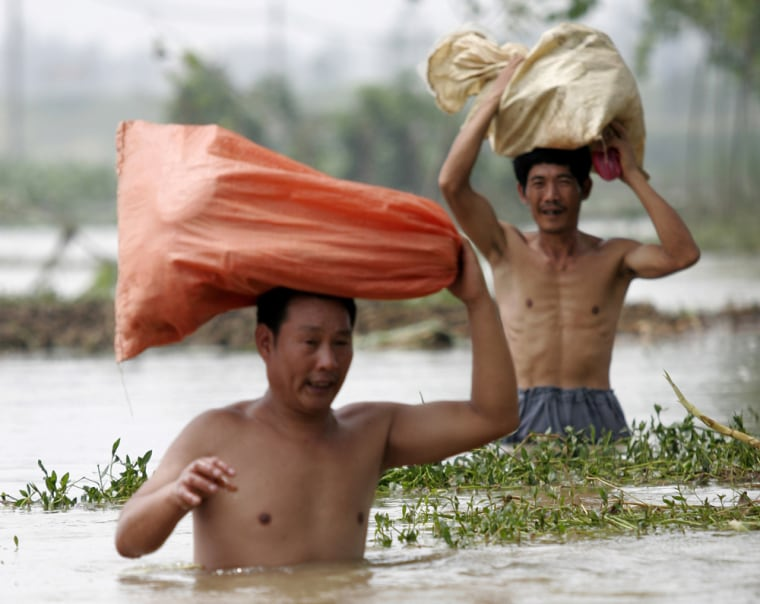 Residents carry bags Thursday through flood waters in Fuyang, in China's eastern Anhui province. Nationwide flooding and rainfall have killed at least 360 people so far this summer nationwide.