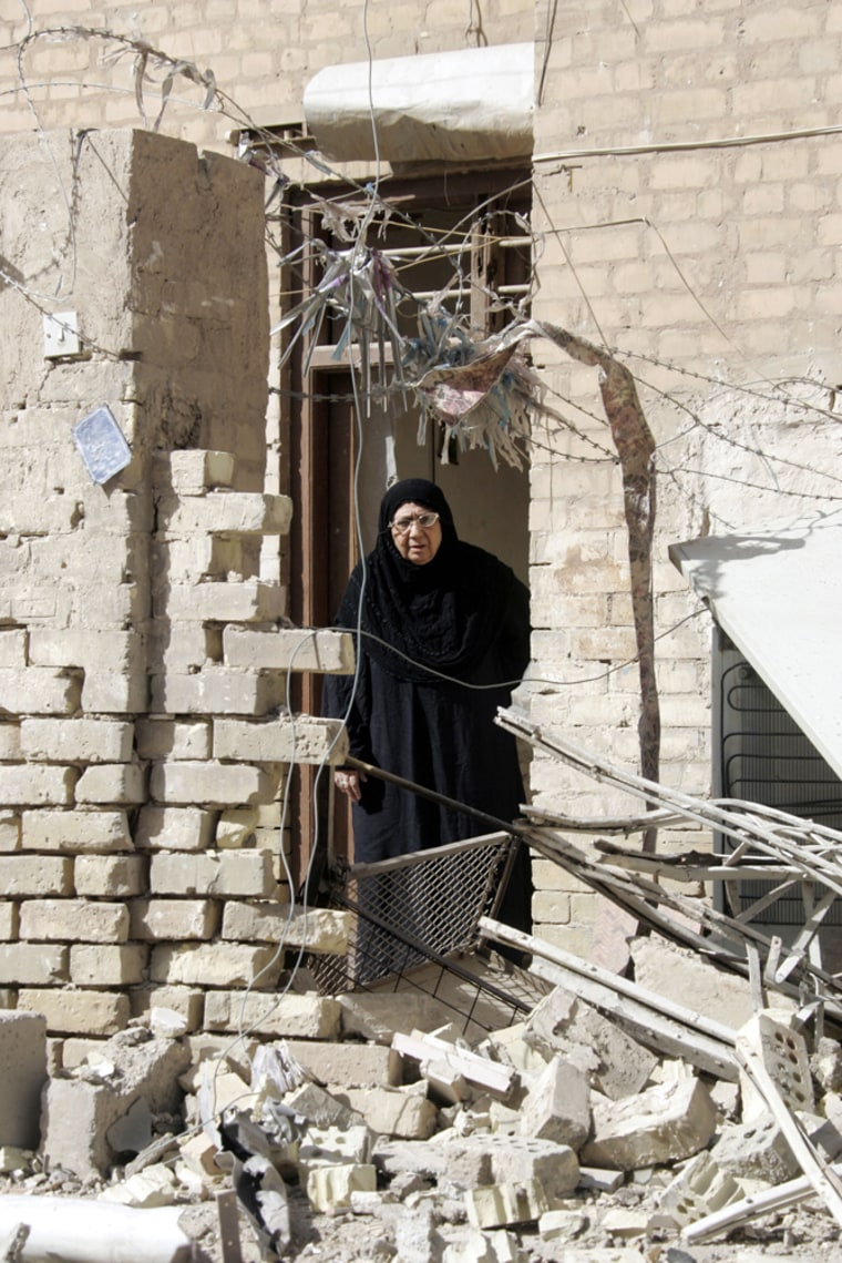 Umm Zuhair, 65, stands in the rubble outside her home after an overnight raid in the Azamiyah neighborhood in Baghdad by U.S. troops Thursday.