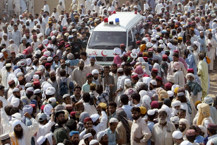 An ambulance carrying the body of late rebel cleric Abdul Rashid Ghazi is surrounded by residents during his funeral in village Basti Abdullah