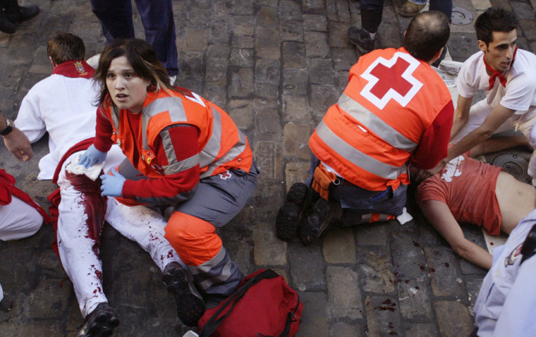 Unidentified runners are attended by medical service personnel during the sixth running of the bulls at the San Fermin festival in Pamplona