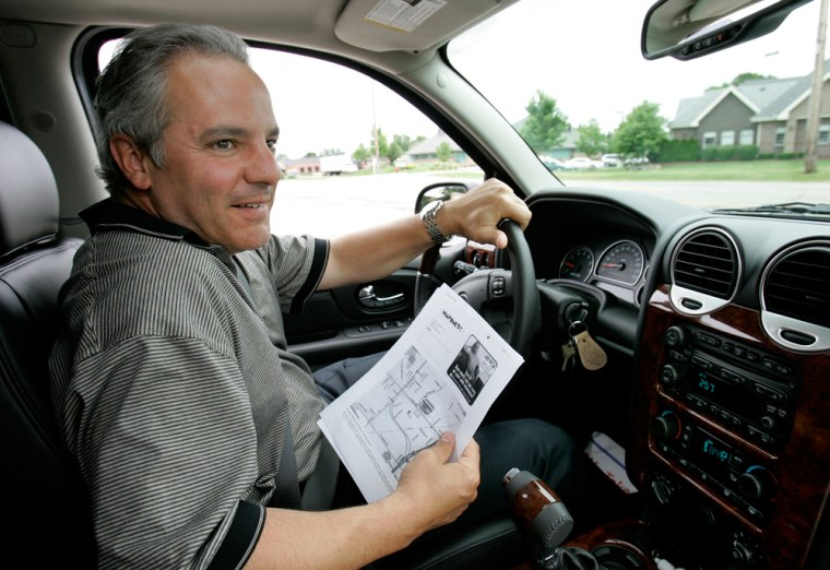 Mark Evangelista uses a copy of directions printed out from a computer while driving in Novi, Mich. The owner of a construction company, who just leased a GMC Envoy for his business, passed on the in-dash navigation system because of the $25 it would add to his monthly payment.