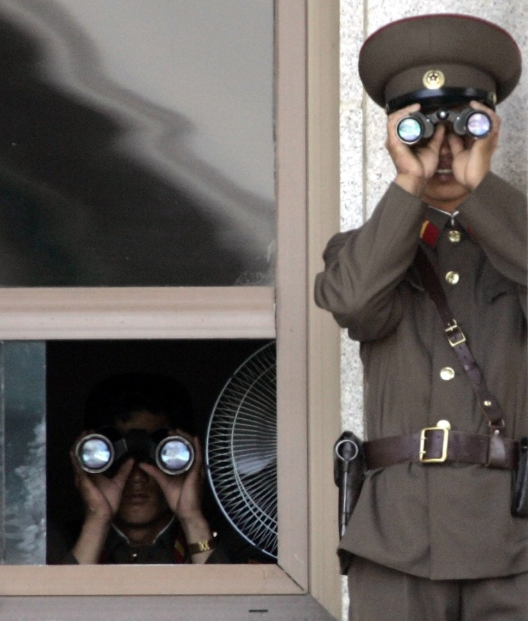 Two North Korean soldiers on the lookout in the demilitarized zone (DMZ) that has separated the two Koreas since the Korean War on Saturday, June 16.